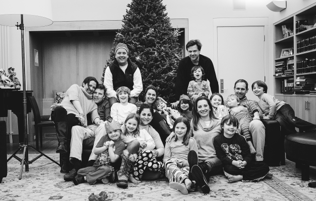 large group photo of adults and kids in front of christmas tree