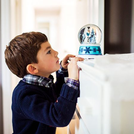 boy looking at snow globe