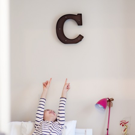 girl pointing to letter C on wall