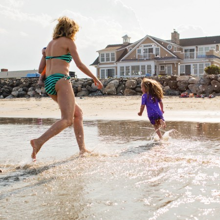 mom chasing daughter at beach