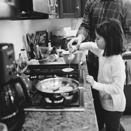 girl making pancakes with father documentary session