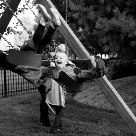 little boy swinging on swingset laughing