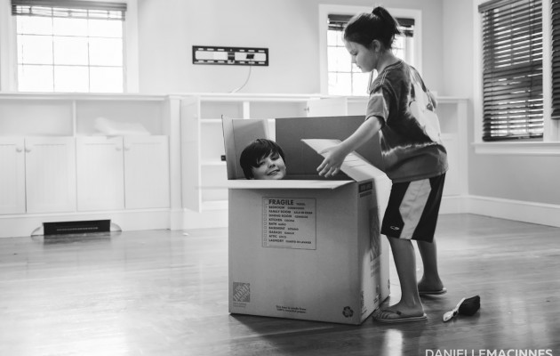 little boy in moving box with girl trying to close it