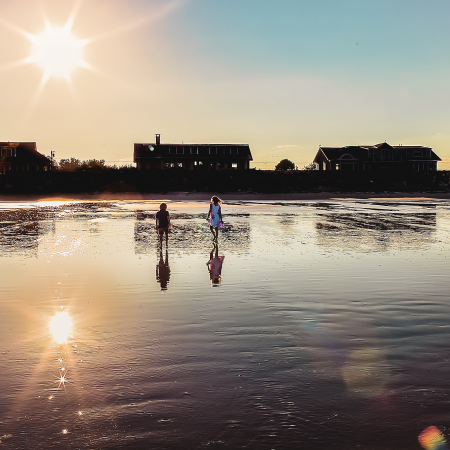 boy and girl walking on beach with sun flare