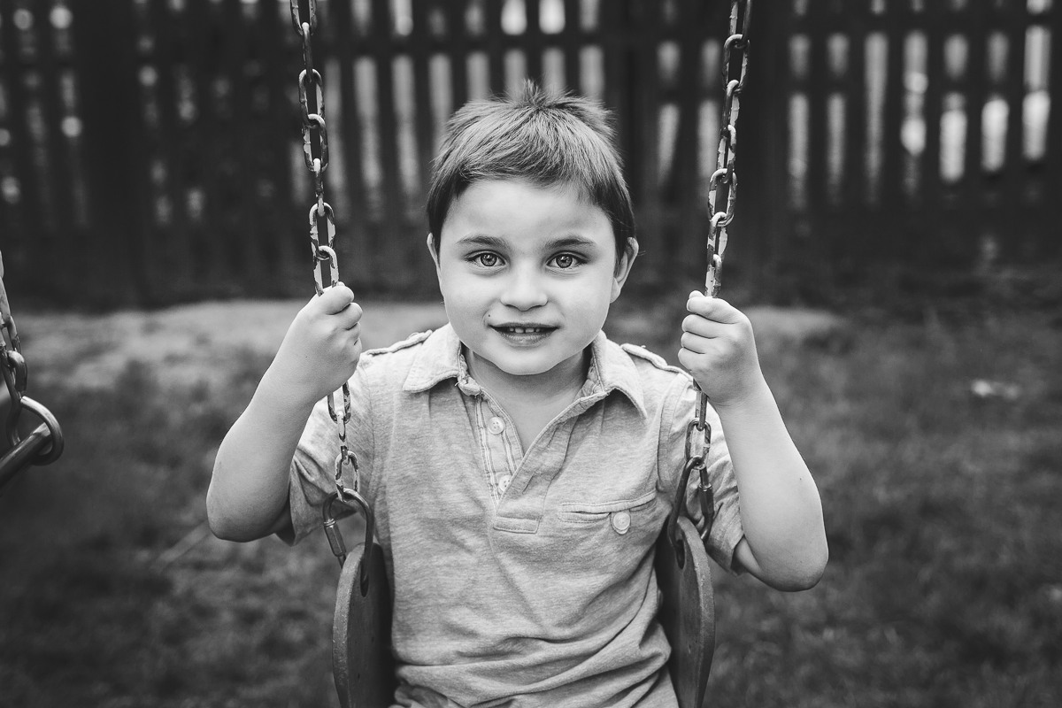 little boy on swing holding on to chains smiling at camera