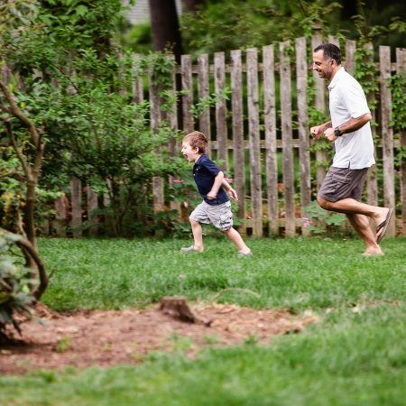 dad chasing little boy in backyard