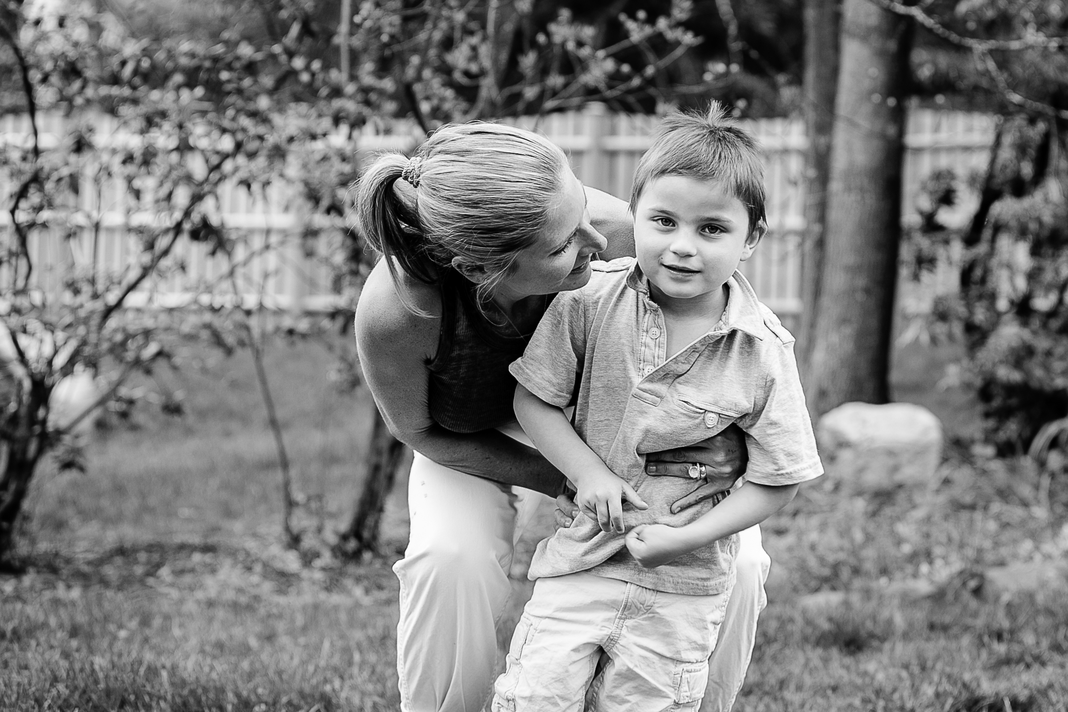 mom hugging little boy outside