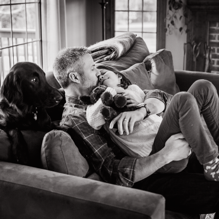 father kissing daughter on couch with dog