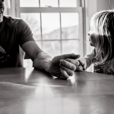 father holding daughter's hand at table