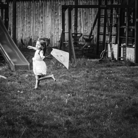 girl running with kite eyes closed