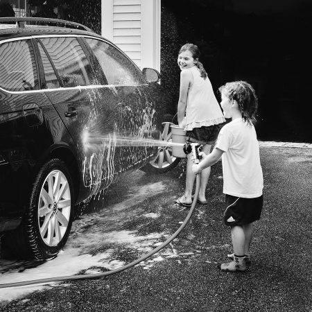 girls washing car hose spray