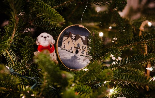 holiday ornament of yellow house in winter