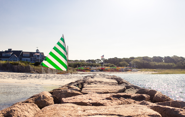 green and white striped sailboat on beach with jetty