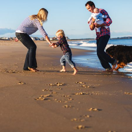 family and dog running at beach