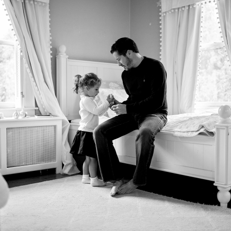 father sitting on bed with daughter having tea party