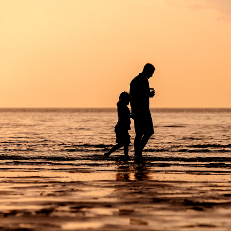 father and daughter silhouette at beach at sunset