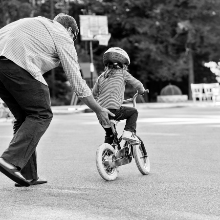 dad holding on to back of little girl learning to ride a bike