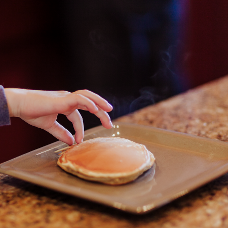 small hand touching hot pancakes on plate