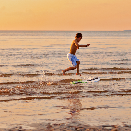 boy jumping onto skim board at the beach at sunset