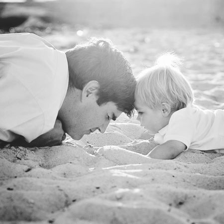 father and son on beach touching heads