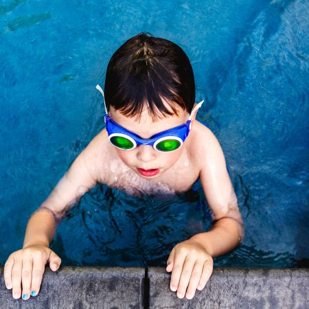 little boy in blue pool with green goggles