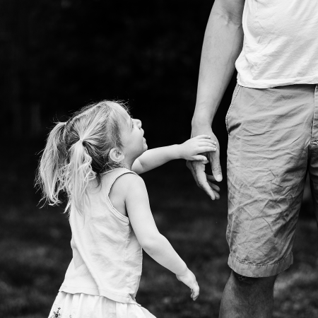 little girl reaching for dad's hand