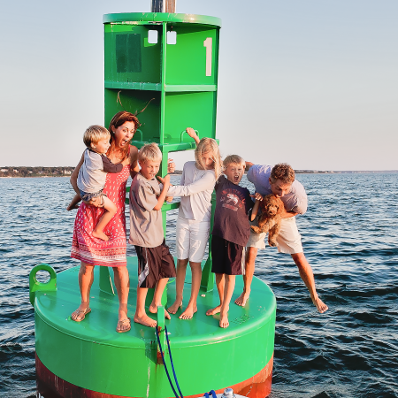 family on green buoy in ocean