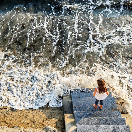 girl on steps of beach surrounded by water
