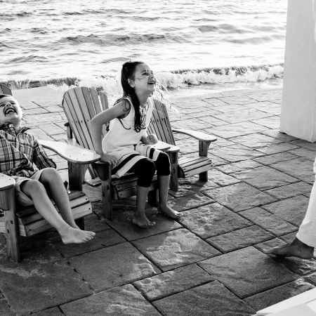two kids sitting in chairs laughing bw