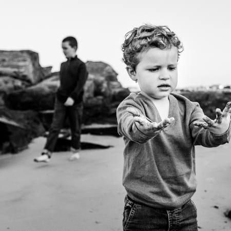 little boy with wet sand on hands at beach