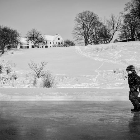child running across frozen pond with house in distance