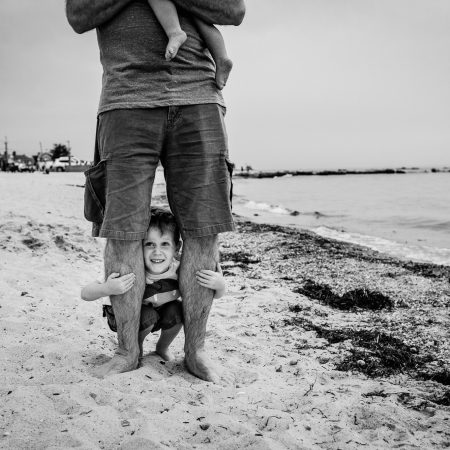 little boy peeking out between dad's legs at beach