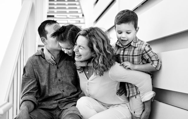 mom dad and two kids laughing on steps