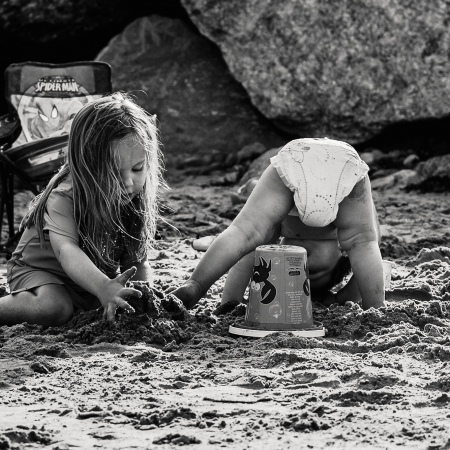 little girl in sand with toddler bending over showing diaper at beach