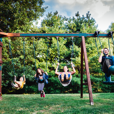 mom, dad, and two daughters on swings