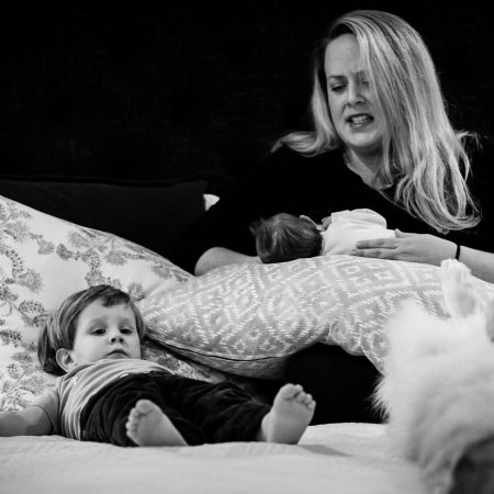 little boy laying in bed exhausted next to breastfeeding mother