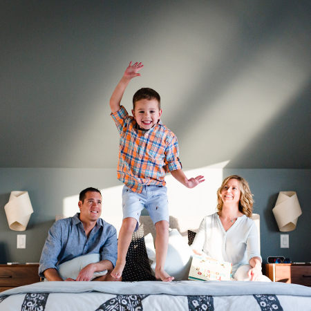 little boy jumping on bed excitedly while parents look on