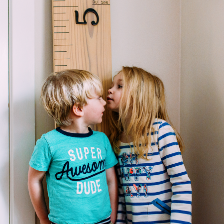 young girl checking to see how tall little brother is