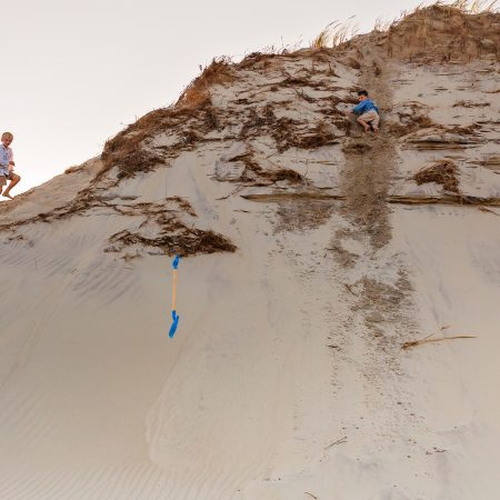 boys looking back and dropped shovel after climbing sand dune