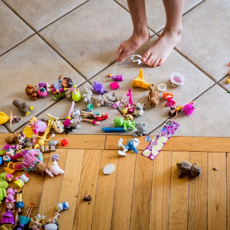 child's feet standing next to a pile of toys
