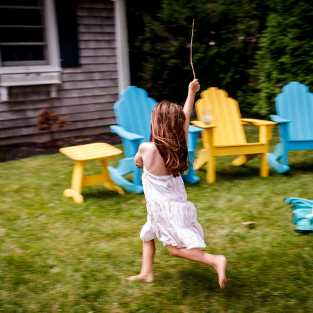 little girl running with stick in hand