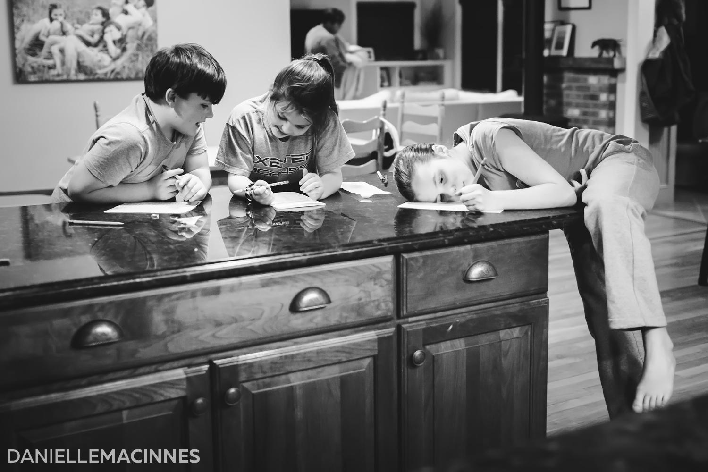 three kids at counter writing