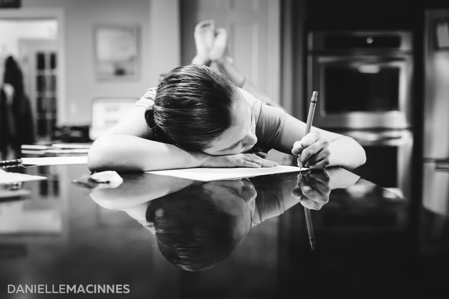 girl laying on counter writing with reflection