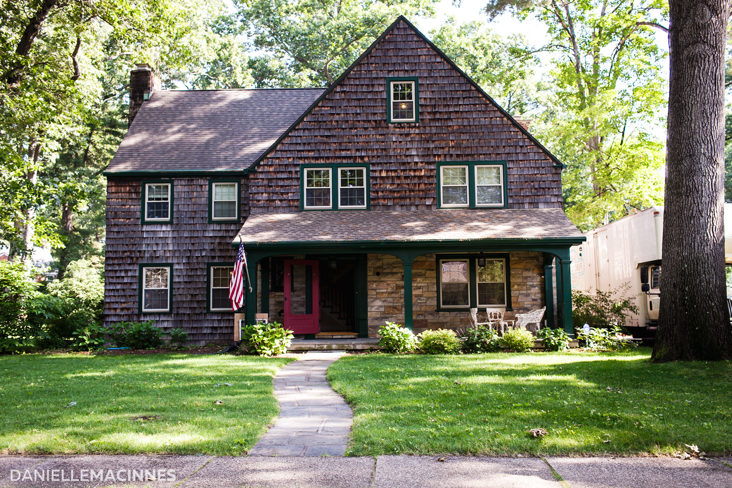 brown shingled House with red door and flag out front