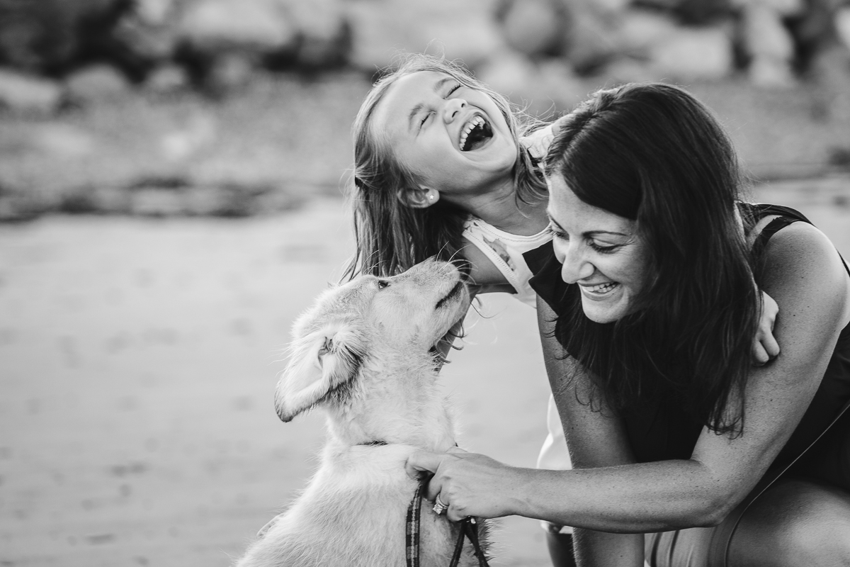 little girl laughing with mom and puppy