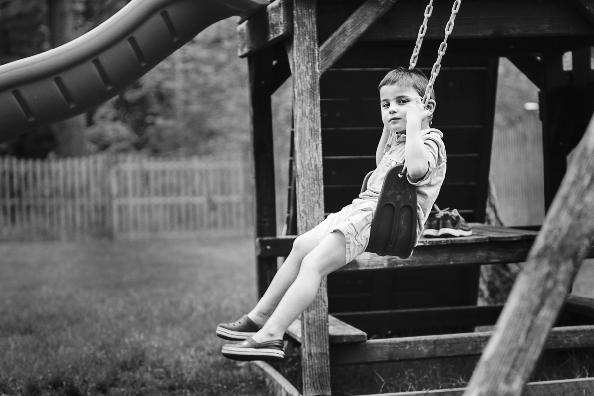 Little boy on swing looking at camera