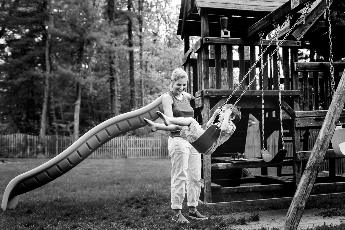 mom smiling at son on swing with barefeet