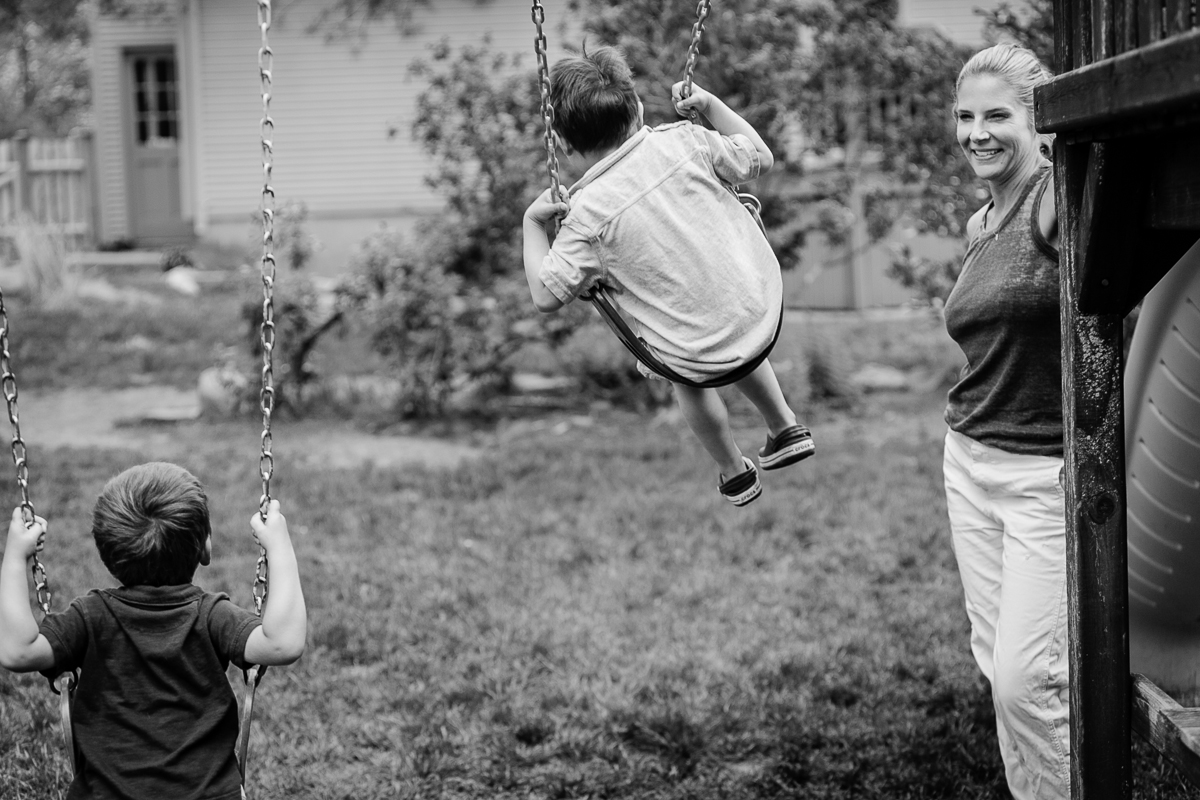back of sons on swing with mom watching