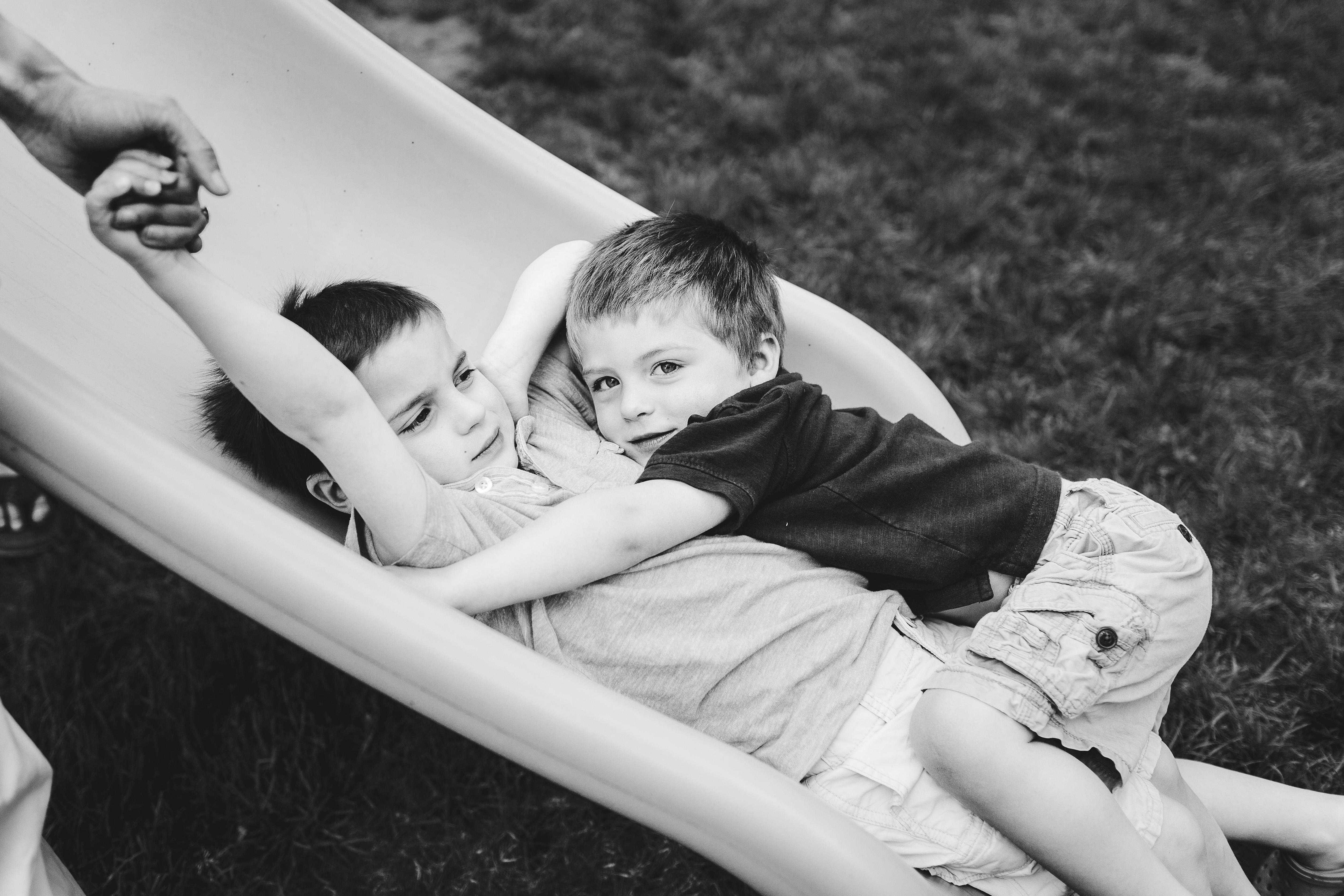 brothers hugging on slide one holding dad's hand