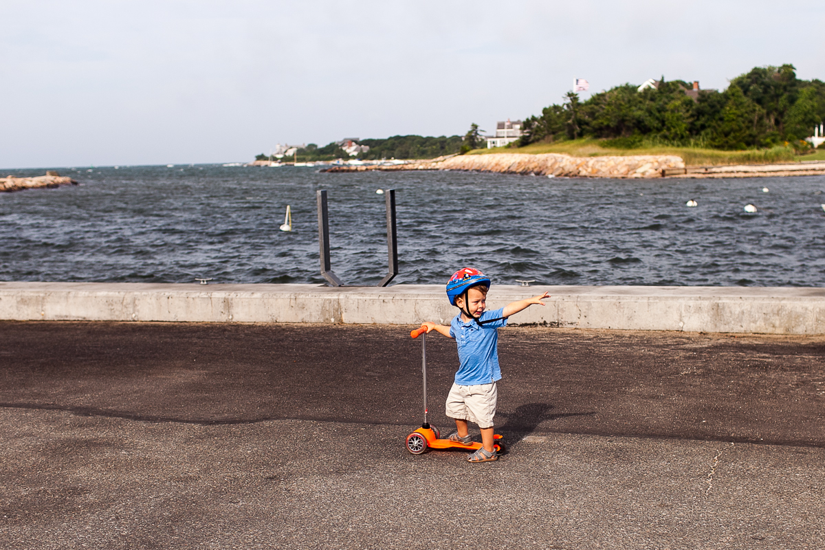 little boy pointing backward on scooter in front of harbor